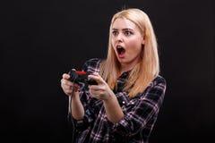 Emotionales gir spielt faszinierend mit Steuerknüppel und erschrocken ihrem Mund Auf einem schwarzen Hintergrund lizenzfreies stockfoto