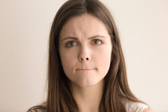 Emotionales Headshotporträt der unentschlossenen jungen Frau Lizenzfreie Stockfotos