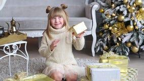 Emotionales kleines Mädchen hält eine Geschenkbox in den Händen, Versuch, um sich nahe Weihnachtsbaum zu Hause zu öffnen stock footage