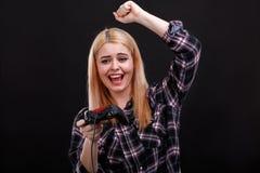 Emotionales Mädchen spielt faszinierend mit dem Steuerknüppel und froh Schreien und oben hebt ihre Hand an Schwarzer Hintergrund stockfotografie