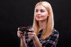 Emotionales Mädchen, spielt faszinierend mit einem Spielsteuerknüppel Auf einem schwarzen Hintergrund stockbilder