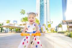 Emotionales nettes kleines blondy Kleinkindmädchen im Kleiderreitroller im Stadtparkerholungsgebiet mit modernem Wolkenkratzergeb stockfotos