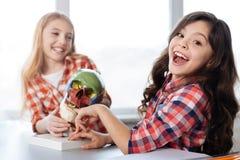 Emotionales nettes Mädchen, das über das Modell lacht Stockfoto