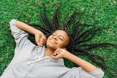 Emotionales Porträt der beweglichen Hände der frohen afroen-amerikanisch Frau beim Legen auf das Gras und Hören Musik lizenzfreies stockfoto