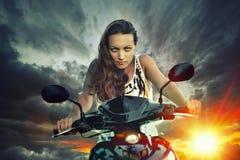 Emotionales Porträt der jungen Schönheit auf einem Motorrad auf Th Lizenzfreie Stockfotos