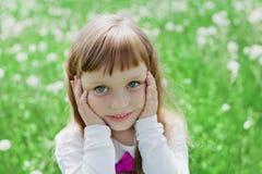 Emotionales Porträt der Nahaufnahme des netten kleinen Mädchens mit den schönen gefühlvollen Augen, die auf einer grünen Wiese st lizenzfreie stockfotos