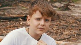 Emotionales Porträt des rothaarigen Jugendlichjungen mit blauen Augen und Sommersprossen, der die Kamera untersucht stock footage