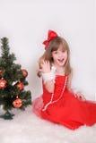Emotionales Porträt eines netten Mädchens im roten Kleid Das Geschenk des neuen Jahres unter dem Baum Stockfoto