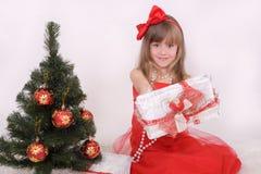 Emotionales Porträt eines netten Mädchens im roten Kleid Das Geschenk des neuen Jahres unter dem Baum Lizenzfreies Stockfoto