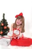 Emotionales Porträt eines netten Mädchens im roten Kleid Das Geschenk des neuen Jahres unter dem Baum Stockbilder