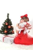 Emotionales Porträt eines netten Mädchens im roten Kleid Das Geschenk des neuen Jahres unter dem Baum Stockbild