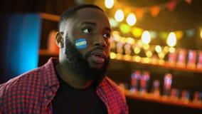 Emotionales schwarzes Fußballfan mit argentinischer Flagge auf der Backe, die facepalm macht stock video footage