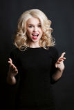 Emotionally blonde girl with curly hair posing at camera with opened mouth and gesturing by hands in different sides. Shocked woma Stock Images
