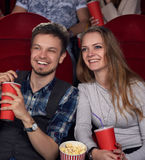 Emotionally couple watching new comedy movie at cinema. Royalty Free Stock Photos