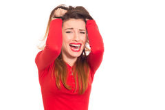 Emotionally stressed woman in red grabbing her hair isolated Stock Photos