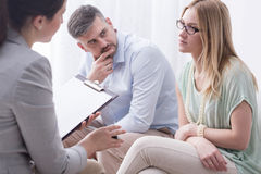 Emotionally tired of constant relationship problems. Upset young women talking to a female psychologist, with her husband aside Stock Image