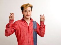 Emotioned guy with golden hairstyle in the red. Shirt showing inverter commas over white background Stock Images
