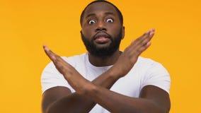 Emotioneel Afro-Amerikaans mannetje die handen kruisen, die gebaar, gele achtergrond waarschuwen stock footage