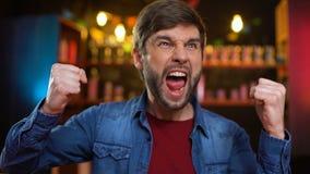 Emotioneel gebaard mannetje die het nationale winnende spel van het voetbalteam, bar vieren stock video