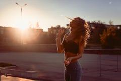 Emotioneel jong meisje in bustehouder en jeans die in de stad van de de zomeravond dansen Stock Foto