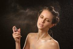Emotioneel manierportret van mooie vrouwen met heldere make-up De fles van het holdingsparfum Het bespuiten van water in motie Na Stock Afbeeldingen