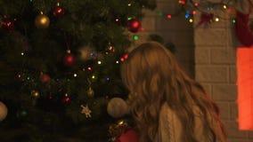 Emotioneel meisje die onder Kerstboom, het vieren vakantie huidig vinden stock videobeelden