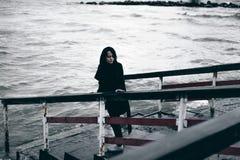 Emotioneel modieus portret van een jonge donkerbruine vrouw in zwarte kleren, jeanst-shirt, laag en zonnebril, in een Gotische st Stock Foto
