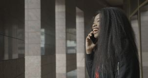 Emotioneel portret van het aanbiddelijke Afrikaanse meisje die terwijl het spreken via de mobiele telefoon in de straat lachen 4k stock footage