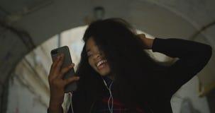 Emotioneel portret van het vrolijke charmante Afrikaanse meisje die door videopraatje spreken en gelukkig in de straat dansen stock footage