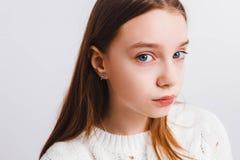Emotioneel tienermeisje in een witte gebreide sweater op een lichtgrijze achtergrond Ruimte voor tekst stock afbeelding