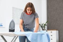 Emotioneel vrouw het strijken overhemd aan boord royalty-vrije stock afbeelding