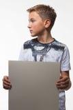 Emotionele blonde jongen in een wit overhemd met een grijs blad van document voor nota's Royalty-vrije Stock Afbeelding