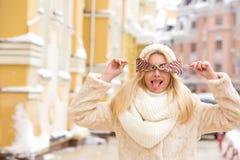 Emotionele blondevrouw met lang haar die warme gebreide hoed dragen, Stock Foto's