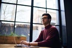 Emotionele freelancer in een jasje die van Bourgondië moderne technologie en vrije draadloze verbinding gebruiken aan Internet Stock Foto