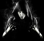Emotionele, jonge en aantrekkelijke moordenaar in handschoenen op de zwarte achtergrond stock fotografie