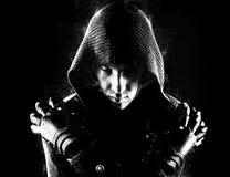 Emotionele, jonge en aantrekkelijke moordenaar in handschoenen op de zwarte achtergrond royalty-vrije stock foto