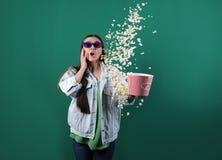 Emotionele jonge vrouw die met 3D glazen popcorn werpen stock foto's
