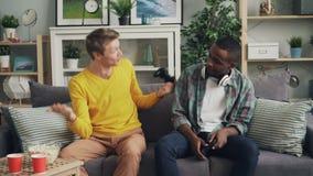 Emotionele jongeren Afrikaanse Amerikaans en Kaukasisch speelt videospelletje die thuis dan zitting op bank spreken bij stock footage