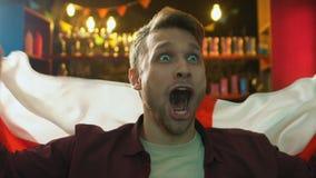 Emotionele mannelijke ventilator golvende vlag van Engeland in bar die nationale teamoverwinning verheugen zich stock footage