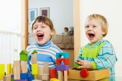 Emotionele siblings die met houten speelgoed spelen Stock Afbeelding