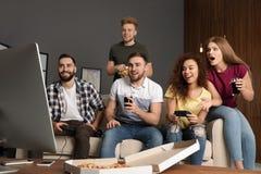 Emotionele vrienden die videospelletjes spelen stock foto's