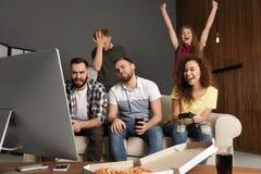 Emotionele vrienden die videospelletjes spelen stock afbeeldingen