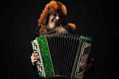 Emotionele vrouw die in bonthoed de harmonika spelen royalty-vrije stock foto