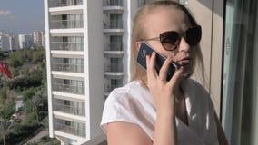 Emotionele vrouw die mobiele telefoonbespreking op het balkon met overzeese mening hebben stock video