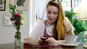 Emotionele vrouw die op mobiele telefoon babbelen terwijl het drinken van thee stock videobeelden