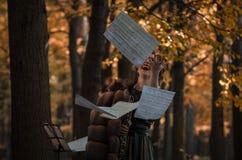 Emotionele vrouw-hoboïst die een hobo houden werpend op de muzikale bladen royalty-vrije stock fotografie