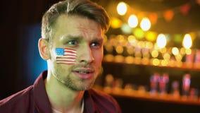Emotionell amerikansk fotbollsfan med flaggan på kinden som ja gör gesten, seger lager videofilmer