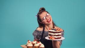 Emotionell blond flickakonditor som rymmer en stor kaka och ler på kameran i studio lager videofilmer