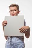 Emotionell blond pojke i en vit skjorta med ett grått ark av papper för anmärkningar Royaltyfri Bild