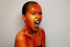 emotionell flicka Härlig Woman ovanlig makeup Framsidakonst Bodypaint Kroppkonst Folk med guld- omfamna för smink Isolerat på grå Royaltyfri Fotografi
